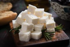 Greek feta cheese. Famous dairy product with black olives and rosemary Royalty Free Stock Photo