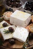 Greek feta cheese. Famous dairy product with black olives and rosemary Stock Photos