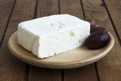 Greek feta cheese with kalamata olives on rustic plate and table.  stock photography