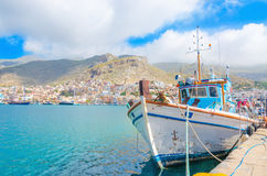 Greek Fishermans' boat standing in harbour with port bui. Typical Greek Fishermans' boat standing in harbour with port building in backgound on Greek Island Royalty Free Stock Image