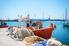 Greek fishing boat stays parked near sea pier at Vlychada town on Santorini island Royalty Free Stock Images