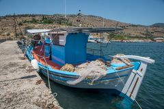 Greek fishing boat tied up at a cement pier royalty free stock photos