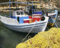 Greek fishing boats. Two colorful Greek fishing boats mored at harbor with bright yellow nets piled in foreground Royalty Free Stock Image