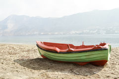 Greek fishing open deck motor boat docked on Telendos island sandy coastline Stock Photo