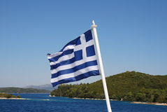 Greek flag. The Greek flag flying from the stern of a ferry boat departing from the Greek island of Lefkada royalty free stock images