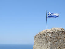 Greek flag in the background of pure blue sky and sea. Royalty Free Stock Images