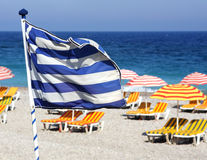 Greek flag on the beach. Fluttering in the wind, the Greek flag on the beach. Welcome to Greece royalty free stock image