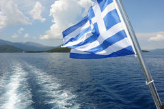 Greek flag and blue sea. Royalty Free Stock Photography