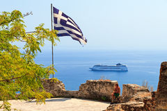 Greek flag cruiseship. Large Greek flag on top of the castle in Zakynthos with a cruiseship in the background Stock Photo
