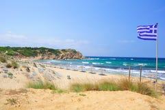 Greek flag and Elias bay beach, Skiathos. Elias bay beach on a particularly windy day, Skiathos island, Sporades archipelago, Greece Royalty Free Stock Photo