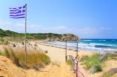 Greek flag and Elias bay beach, Skiathos. Elias bay beach on a particularly windy day, Skiathos island, Sporades archipelago, Greece Royalty Free Stock Photos