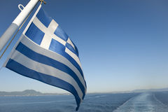 Greek flag at the end of a boat. Against blue sky Stock Photos