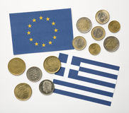Greek flag and European flag with Euros and Drachma coins Stock Images