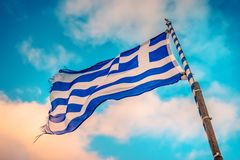 Greek flag on the flagpole. Under evening sky stock photos