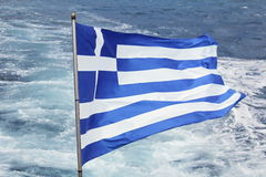 Greek Flag Fluttering With Sea Waves In Background. View from a boat Stock Image