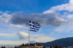 Greek flag flying against dramatic sky on Acropolis with tourists standing around it Athens Greece 01 03 2018 Stock Photo