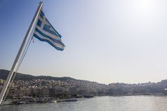 Greek flag flying on the wind, city and sea in the background stock photo