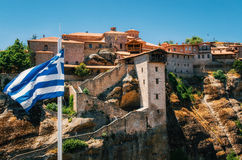 Greek flag in front of The Holy Monastery of Great Meteoron in Meteora, Greece Royalty Free Stock Photo