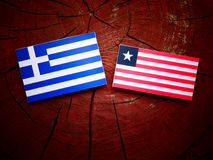 Greek flag with Liberian flag on a tree stump isolated. Greek flag with Liberian flag on a tree stump Stock Image
