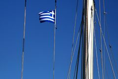 Greek flag on the mast of a sailing boat. Travelling in the blue sea, summer in Greece. stock photo