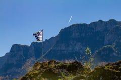 Greek flag and mountains above Vikos gorge, Epirus, Greece Royalty Free Stock Images