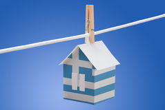 Greek flag printed on paper house. Concept - Greek flag printed on a paper house hanging on a rope Royalty Free Stock Photo