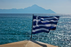 Greek flag on a sailing ship with holy mountain Athos in background Royalty Free Stock Photo