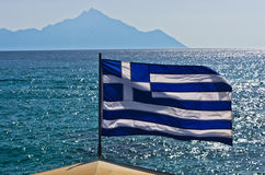 Greek flag on a sailing ship with holy mountain Athos in background Stock Photo