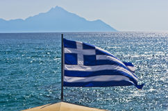 Greek flag on a sailing ship with holy mountain Athos in background Royalty Free Stock Images