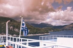 The Greek flag on the ship against the background of the sea of islands. Sea voyage in the Ionian sea. Stock Photography