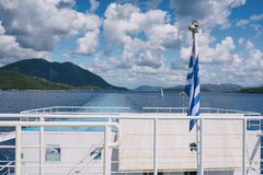 The Greek flag on the ship against the background of the sea of islands. Sea voyage in the Ionian sea. Stock Image