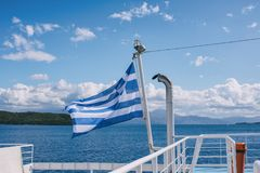 The Greek flag on the ship against the background of the sea of islands. Sea voyage in the Ionian sea. Royalty Free Stock Images