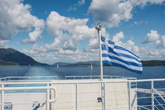 The Greek flag on the ship against the background of the sea of islands. Sea voyage in the Ionian sea. Royalty Free Stock Photo