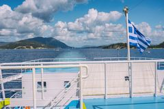 The Greek flag on the ship against the background of the sea of islands. Sea voyage in the Ionian sea. The Greek flag on the ship against the background of the Stock Image