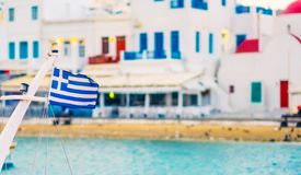 Greek flag on ship. With blurred houses at background royalty free stock images