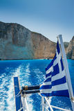 Greek Flag, Shipwreck Beach, Navagio in Zakynthos, Greece. Navagio - the most famous beach on Zakynthos island with shipwreck and anchoring boats (Greece, Ionian Royalty Free Stock Images