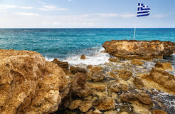 Greek flag on the shore with beautiful view of bay in southwest of the island of Crete. Greece. Europe. Greek flag on the shore with beautiful view of bay in Stock Photos
