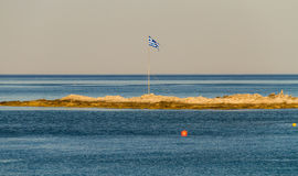 Greek flag on small piece of land in the sea Royalty Free Stock Photography