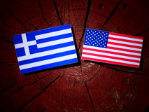 Greek flag with USA flag on a tree stump royalty free stock image