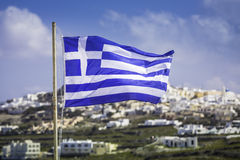 Greek Flag waving with overview  of Santorini Island Royalty Free Stock Images