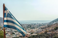 Greek flag waving at Pothia cityscape the capital Royalty Free Stock Photos