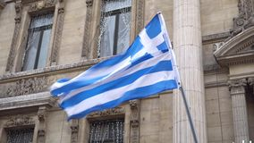 Greek flag waving on the strong wind on the background of buildings.  stock video