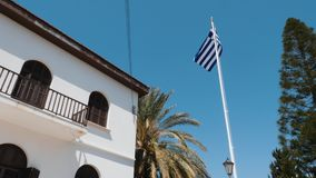 Greek flag waving in wind against blue clear sky. Bottom view of part of white building with Greek flag stock video