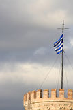 Greek flag on white tower. Against dark sky Royalty Free Stock Photography