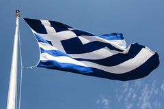 Greek flag in the wind against a blue Summer sky Stock Image
