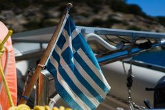 Greek flag on a yacht. Greek flag on a yacht with a view of mountains and blue sky royalty free stock photo