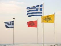 Greek flags against the sky. Stock Photos