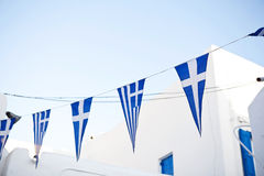 Greek flags on cyclades. Traditional white house on background Stock Photos