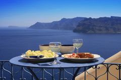 Greek food. And wine with view of Santorini and the Aegean sea Royalty Free Stock Photo