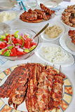 Greek food. Variety of traditional Greek grilled meat and salad served on table Royalty Free Stock Image